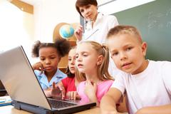 photo of serious classmates and teacher looking at the laptop - stock photo