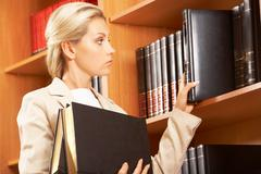 Profile of confident woman standing by the bookshelf and choosing books Stock Photos