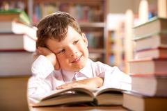 Portrait of smiling schoolboy sitting at the table with books on it Stock Photos
