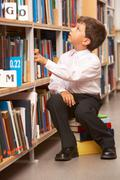 portrait of diligent schoolboy looking at bookshelf in the library - stock photo