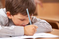 photo of clever schoolkid writing something in his copybook at lesson - stock photo