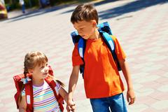 Portrait of smart friends with backpacks walking down city road on sunny day Stock Photos
