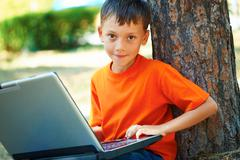 portrait of smart boy with laptop sitting by tree trunk and looking at camera - stock photo