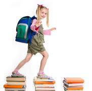 Portrait of girl with backpack walking from top to top of book piles Stock Photos