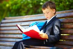 portrait of smart boy sitting in the park and reading interesting book in free t - stock photo