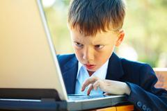 portrait of smart boy working with laptop with attention - stock photo