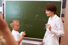 photo of elementary student writing formulae on blackboard with his teacher near - stock photo