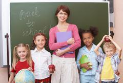 Line of cute schoolchildren looking at camera with their teacher in the middle Stock Photos