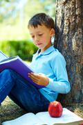 portrait of smart boy in the park and reading interesting book in free time - stock photo