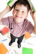 fisheye shot of diligent boy with book on his head while doing homework - stock photo