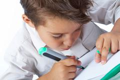 close-up of school boy drawing picture on paper - stock photo