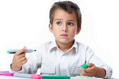 Portrait of smart school boy looking aside and thinking what to draw Stock Photos