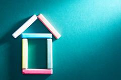 Close-up of colorful pieces of chalk put in form of house on blackboard Stock Photos