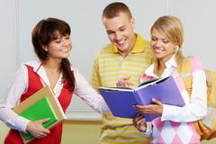 portrait of three friends standing in classroom and discussing lessons - stock photo