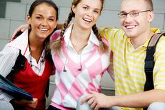 Portrait of two girls and a guy in casual clothes looking at camera happily Stock Photos