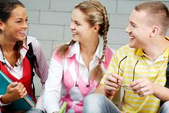 Image of three attractive students chatting before lesson Stock Photos