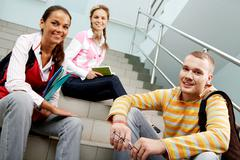 portrait of three teens sitting on stairs and looking at camera in college - stock photo