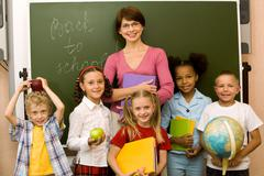 Group schoolchildren looking at camera with their teacher near by Stock Photos