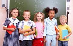 Image of curious schoolchildren standing by blackboard and looking at camera in Stock Photos