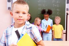 Image of smart schoolboy looking at camera with smile on background of classmate Stock Photos