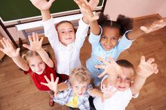 Image of cute schoolchildren looking at camera and laughing with their arms rais Stock Photos