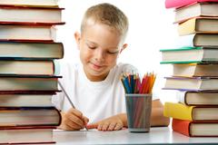 Portrait of cute youngster sitting among stacks of literature and drawing Stock Photos