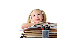 Portrait of cute schoolgirl keeping her arms on open book and looking upwards Stock Photos