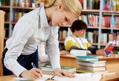 Portrait of serious blonde preparing lessons in college library Stock Photos