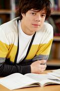 portrait of clever student sitting in front of open book in college library - stock photo