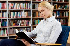 Portrait of clever student with open book reading it in college library Stock Photos