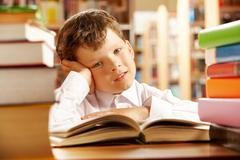 Portrait of a schoolboy sitting at table piled with books Stock Photos