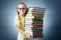 image of happy schoolgirl with stack of books looking at camera - stock photo