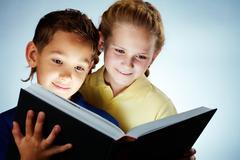 image of smart children reading interesting book - stock photo