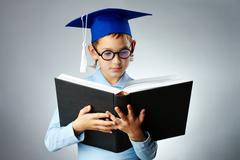 Portrait of cute lad in eyeglasses and student hat reading book Stock Photos
