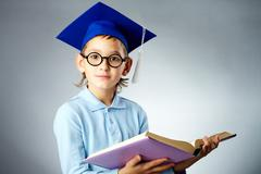 Portrait of cute lad in eyeglasses and student hat holding open book Stock Photos