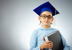 portrait of cute lad in eyeglasses and student hat with book looking at camera - stock photo