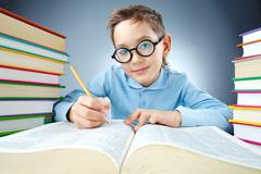 portrait of cute lad in eyeglasses making notes in book and looking at camera - stock photo