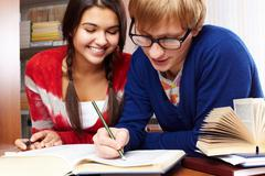 portrait of clever students preparing lessons together in college library - stock photo