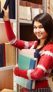 portrait of happy girl in library looking at camera - stock photo