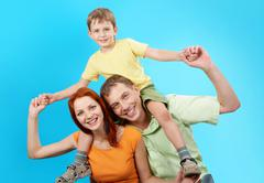 Image of mom and dad with their kid on the shoulders Stock Photos