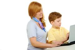photo of cute preschooler and his mother looking at laptop monitor while typing - stock photo