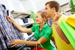 portrait of young couple looking at clothes in department store - stock photo