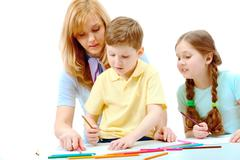 photo of cute preschoolers and their mother drawing - stock photo