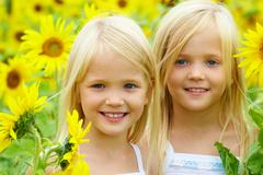 portrait of cute sisters in sunflower field - stock photo