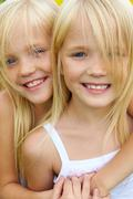portrait of cute girl embracing her twin sister and both looking at camera with - stock photo