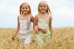portrait of cute twins walking down wheat field and smiling - stock photo