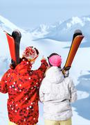 back view of sporty couple with skis at winter resort - stock photo