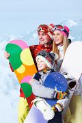 portrait of happy family with snowboards on winter resort - stock photo
