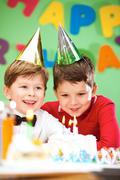 portrait of happy boys on birthday party with cake near by - stock photo