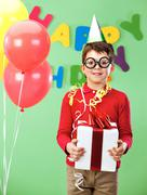 portrait of happy lad in funny eyeglasses on birthday party with giftbox - stock photo